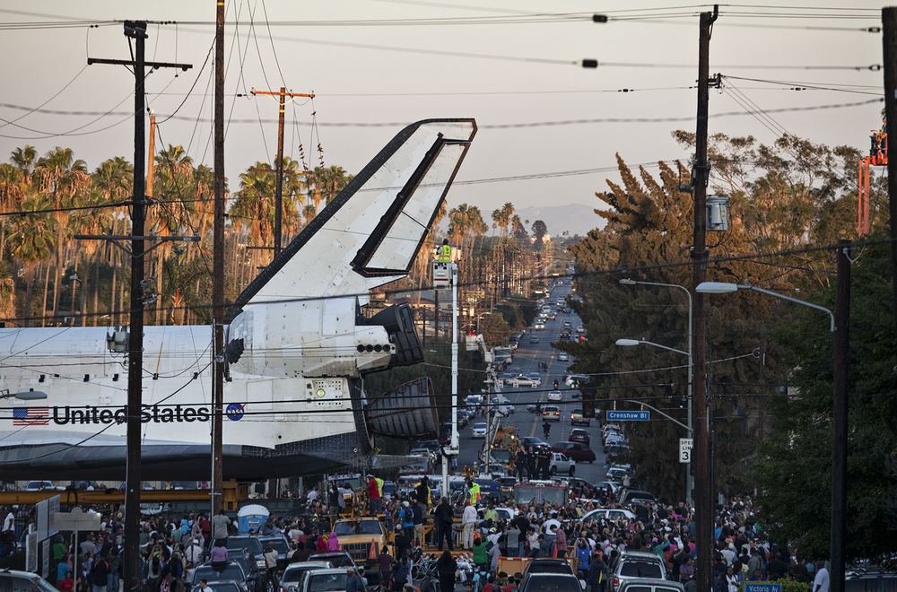 Space shuttle Endeavour makes its way through a Los Angeles neighborhood during a 12-mile land journey from the Los Angeles International Airport to the California Science Center, which is now its home.