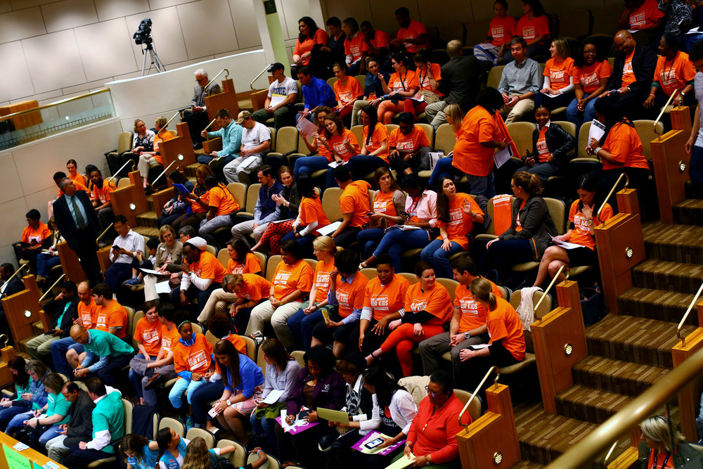 Many of the audience members at a school board meeting on April 12 show their allegiances through their shirts.  Those in green want to keep their neighborhood schools, while the orange shirts support changes to the student assignment policies.