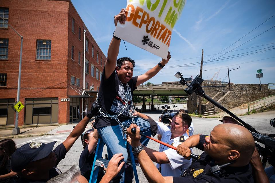 """""""We are defending the security and stability of our families.""""Carlos Medina blockades the street outside ICE's Atlanta Field Office. Photo courtesy Steve Pavey / Hope in Focus www.stevepavey.com"""