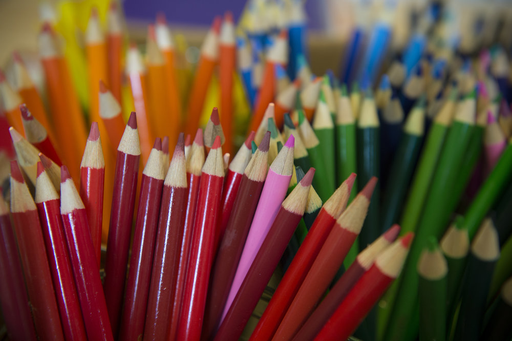 A collection of colored pencils on the desk, symbolic of the school's diversity of students, staff, parents and volunteers.