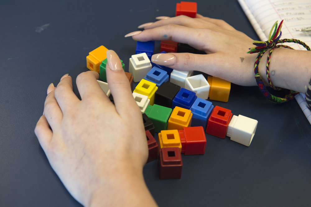 A student prepares for an algebra exercise using multi-colored Lego pieces.