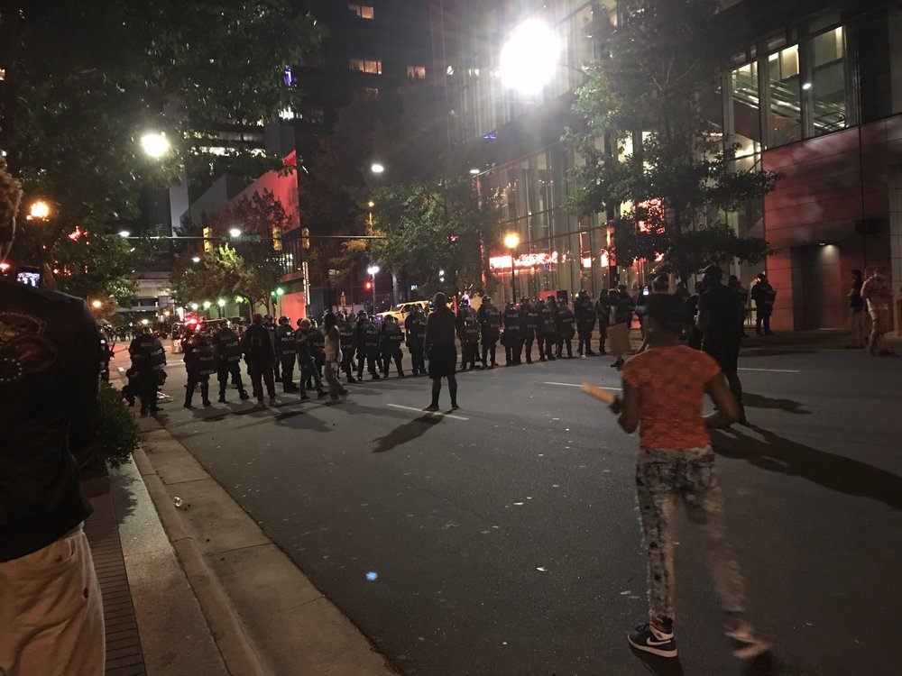 Protesters and armored police in downtown Charlotte. Photo by Danielle Purifoy.