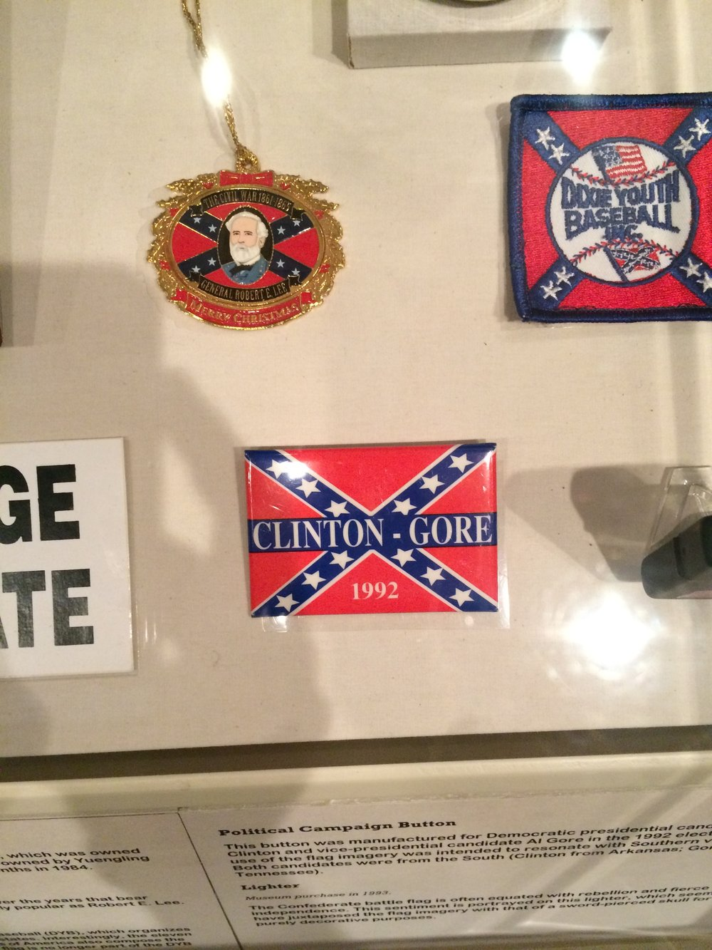 An assortment of objects incorporating the ANV flag into their design, including a 1992 Clinton-Gore campaign button, at the Museum of the Confederacy.