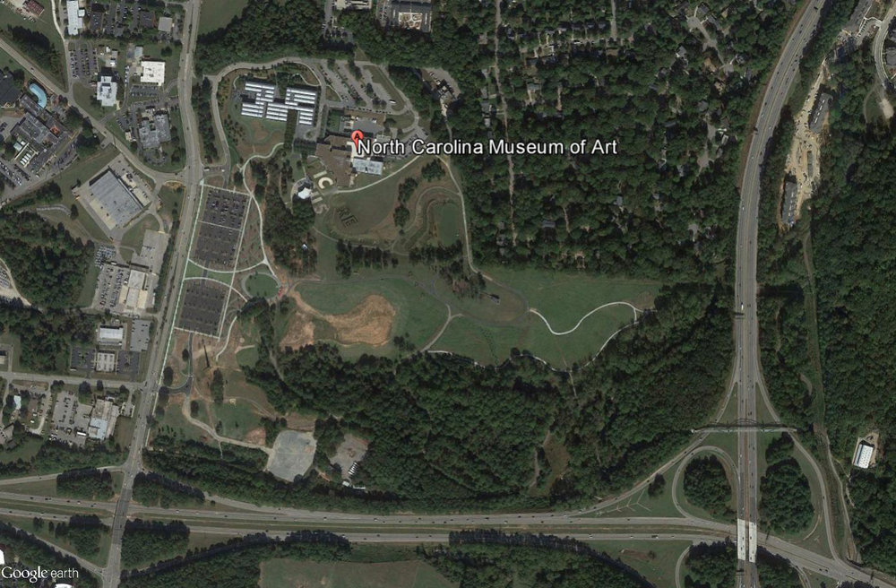 A contemporary aerial photograph of the NCMA site circa 2016. This photo shows the NCMA park and new addition (middle left of the photo) as well as the rapid development that now surrounds the park. (photo credit: Google Earth)