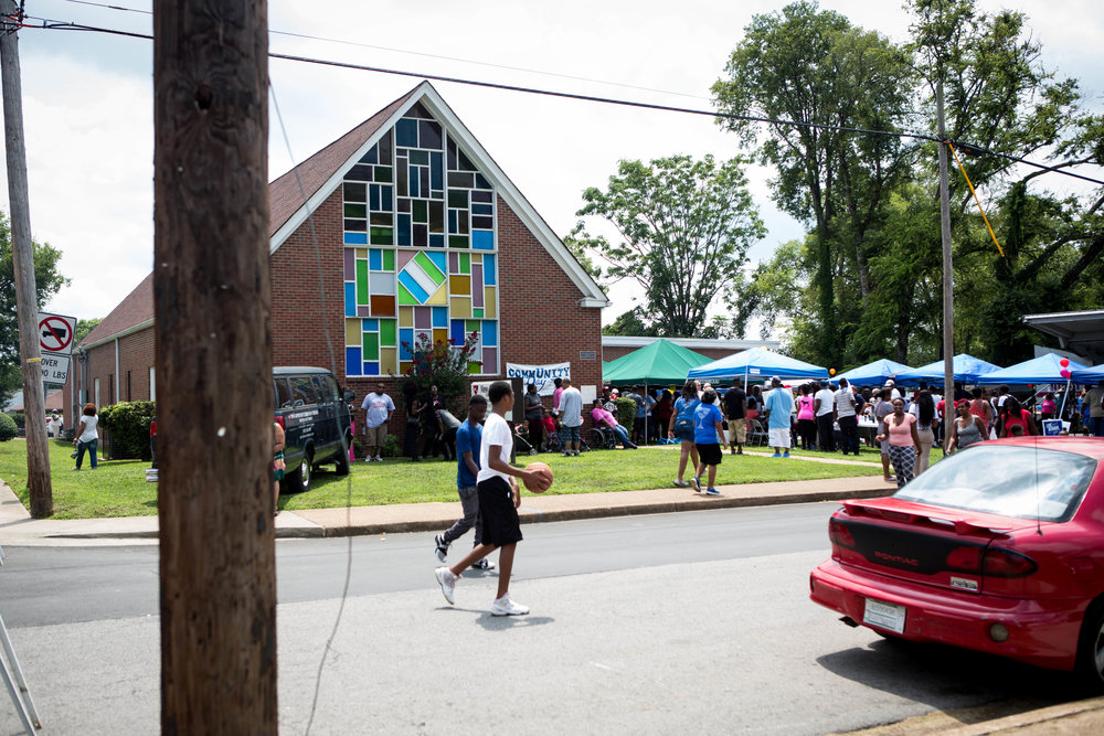 Two boys walk past the New Covenant Church in East Nashville, which was hosting a back-to-school bash for the neighborhood.