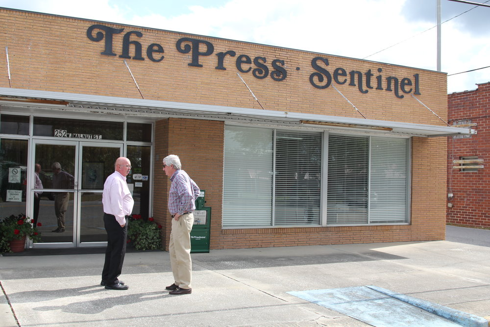 """W.H. """"Dink"""" NeSmith (right) talks to a Wayne County resident outside the offices of the Press-Sentinel, the newspaper he's owned for more than 30 years.""""The Press-Sentinel did what we believe a newspaper's supposed to do,"""" NeSmith said. """"If you can't stand up for the places and the people you love, what kind of newspaper, or person, are you?"""" Photo by Georgina Gustin."""