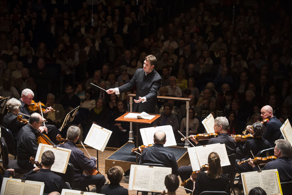 Brett Mitchell, who will become music director of the Colorado Symphony in 2017, leading the Cleveland Orchestra in concert. (Photo by Roger Mastroianni)