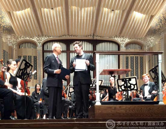 Anthony Yen presents Brett Mitchell with commendations from the Cleveland mayor and the Confucius Institute on Friday, May 12 at Severance Hall. (Photo by Zhang Xuhong