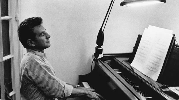 Leonard Bernstein at the piano. Brett Mitchell will lead two concerts celebrating Bernstein's centennial with the New Zealand Symphony Orchestra this month in Wellington and Auckland. (Photo by Getty Images)