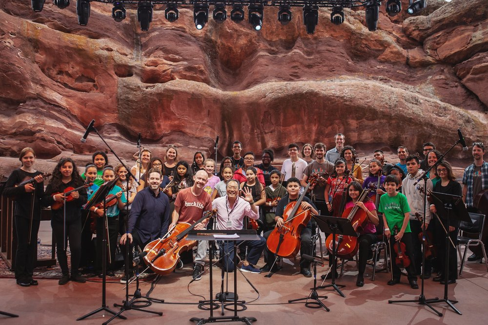 Brett Mitchell, Isaac Slade (lead singer of The Fray), Yo-Yo Ma, and El Sistema Colorado pose for a group photo after a rehearsal at Red Rocks Amphitheater in Morrison, CO. (Photo by Amanda Tipton)