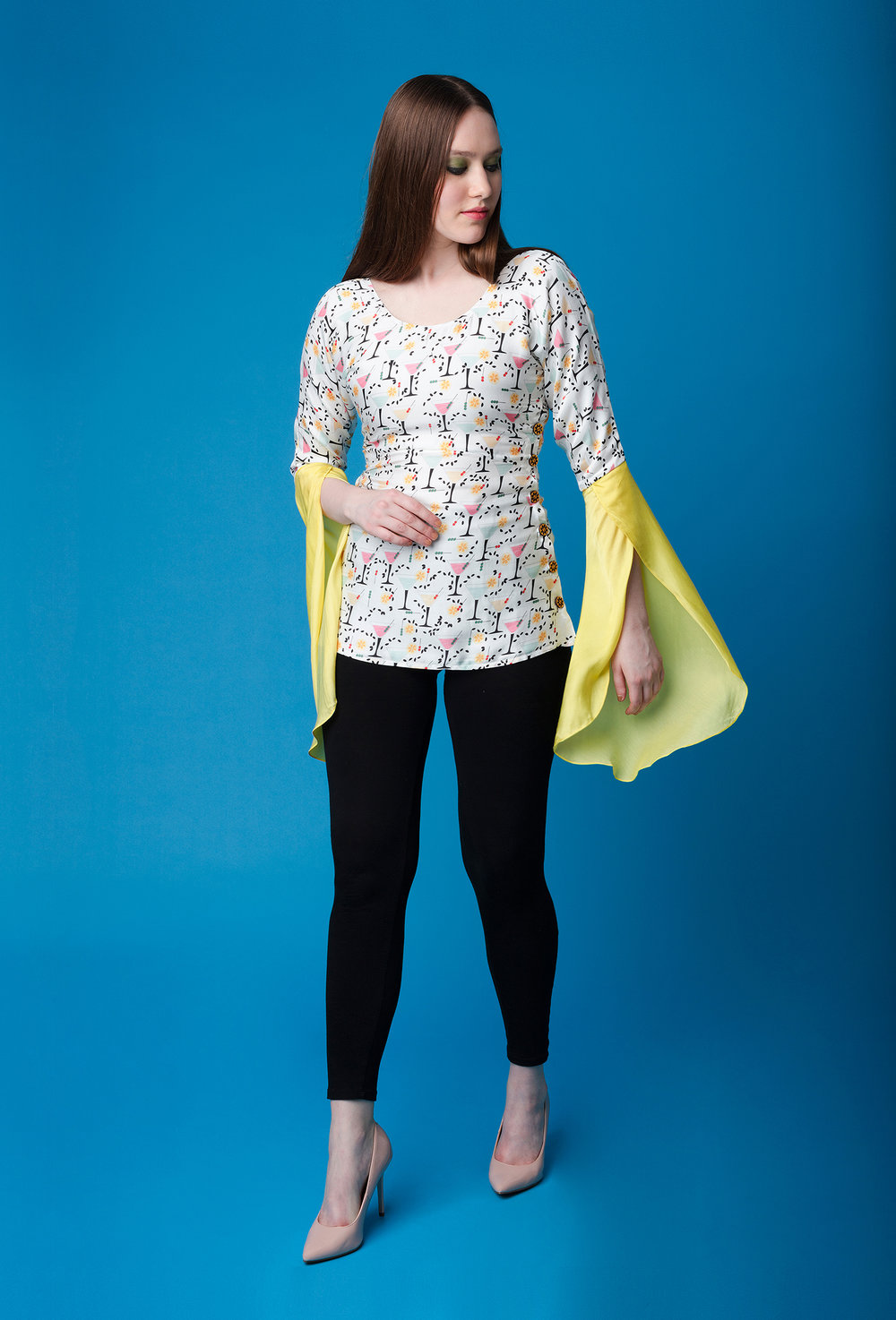 FLIRTINI TOP   A dropped shoulder top with an empire waistline. The sleeves end in an exaggerated open yellow flounce, which adds a bit of drama to the piece. The top has functional yellow wooden buttons along either side . It is made from cotton silk in our Martini print and is fully lined with malai silk.  Dry clean only.   Size :  S, M, L, XL, C  Code :  0106FTY