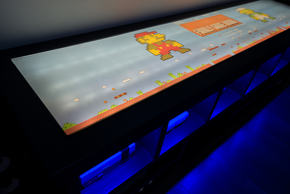The top of the media console features a dual layer of buffed out plexiglass, diffusing the 60-plus underlying LED bulbs that illuminate the clear vinyl graphics on top.