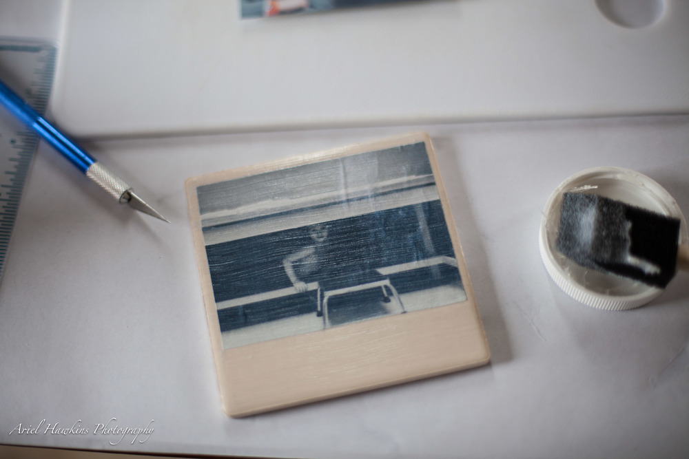 Apply Mod Podge to your picture on the backside. Apply it to your ceramic or wood coaster as well. Line your picture up and use the roller to flatten out any bubbles in your picture.