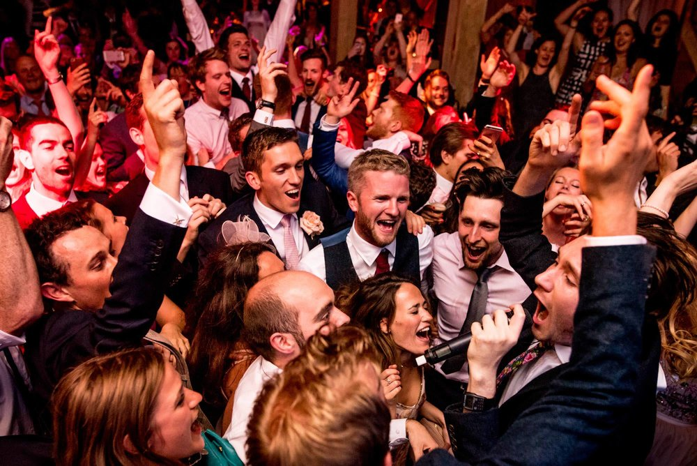 Professional photograph of a crowd singing during a wedding reception