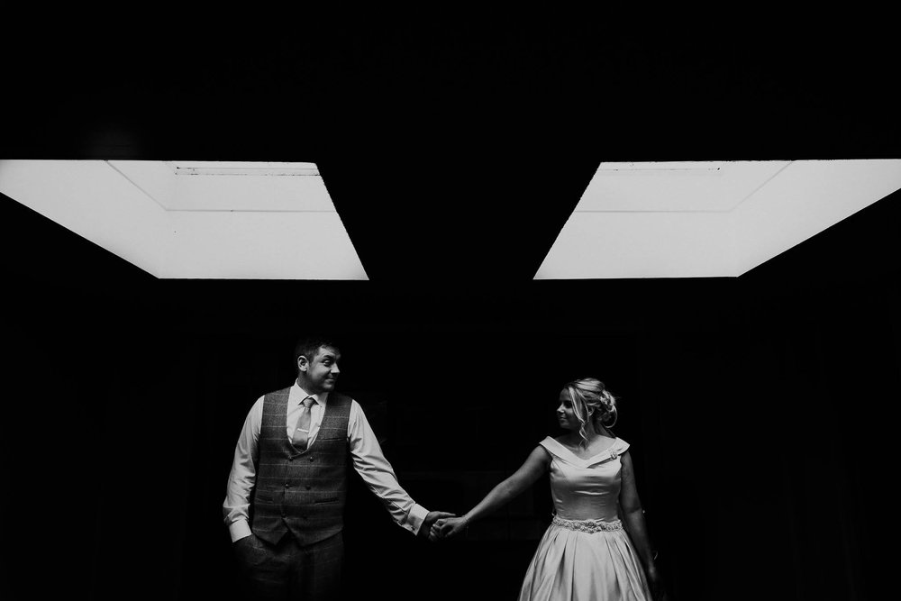 professional photography of a bride and groom holding hands in the dark on their weddingay