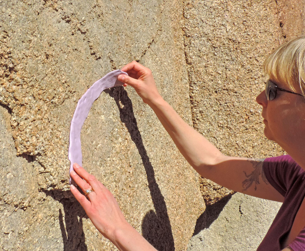 Carefully removing a silicone bracelet mold from a granite wall at Joshua Tree National Park, California.