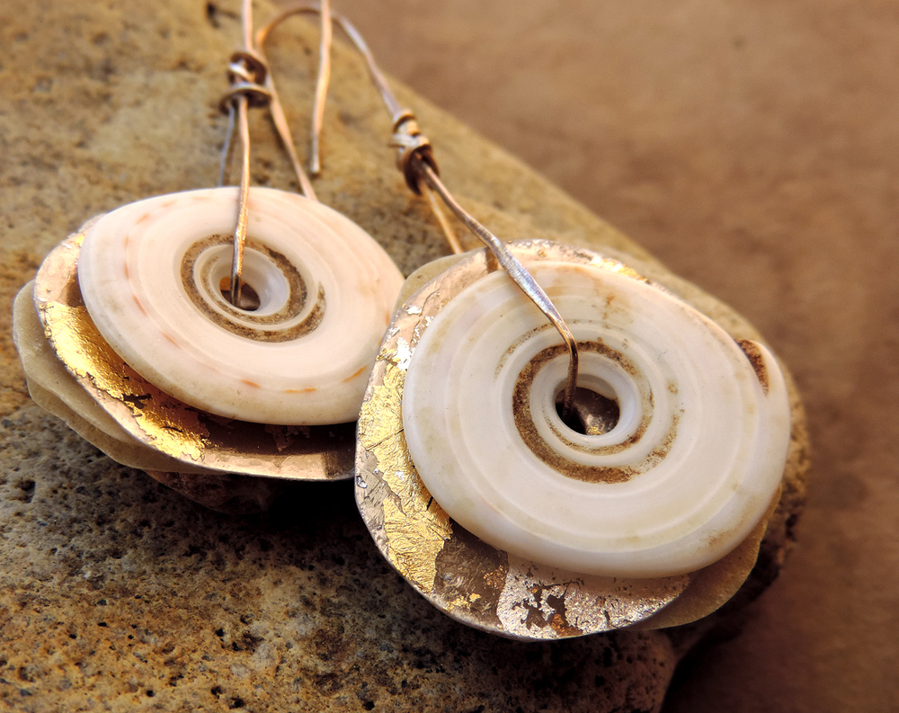 Layered earrings with antique shell currency, mica with metal leaf and resined papers on hammered silver ear wires.