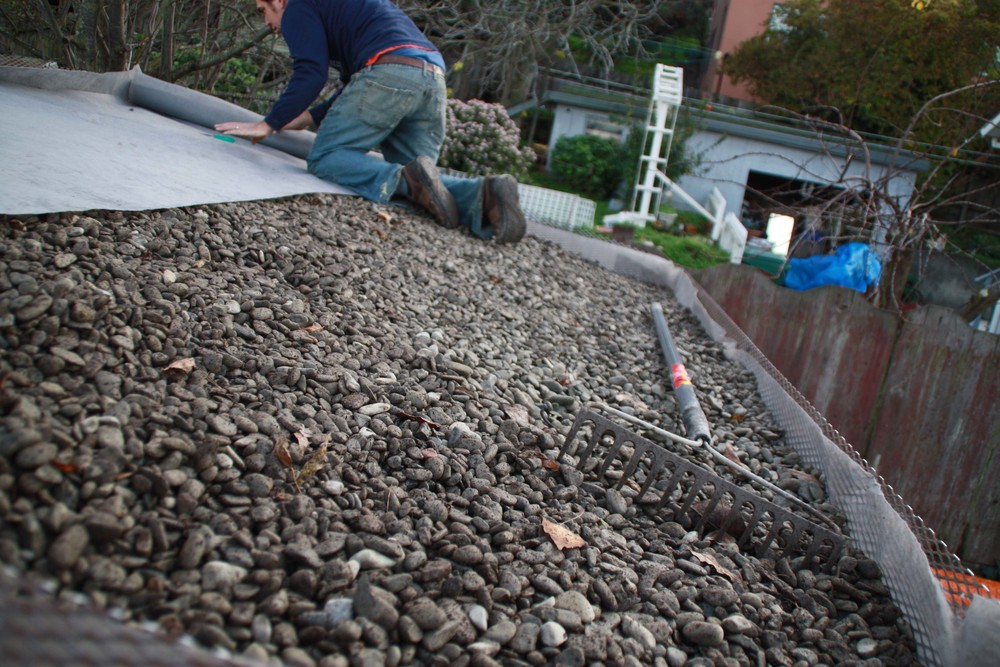 Gravel is placed on top of the root barrier for drainage and filter fabric is placed on top of gravel to keep it free from soil.