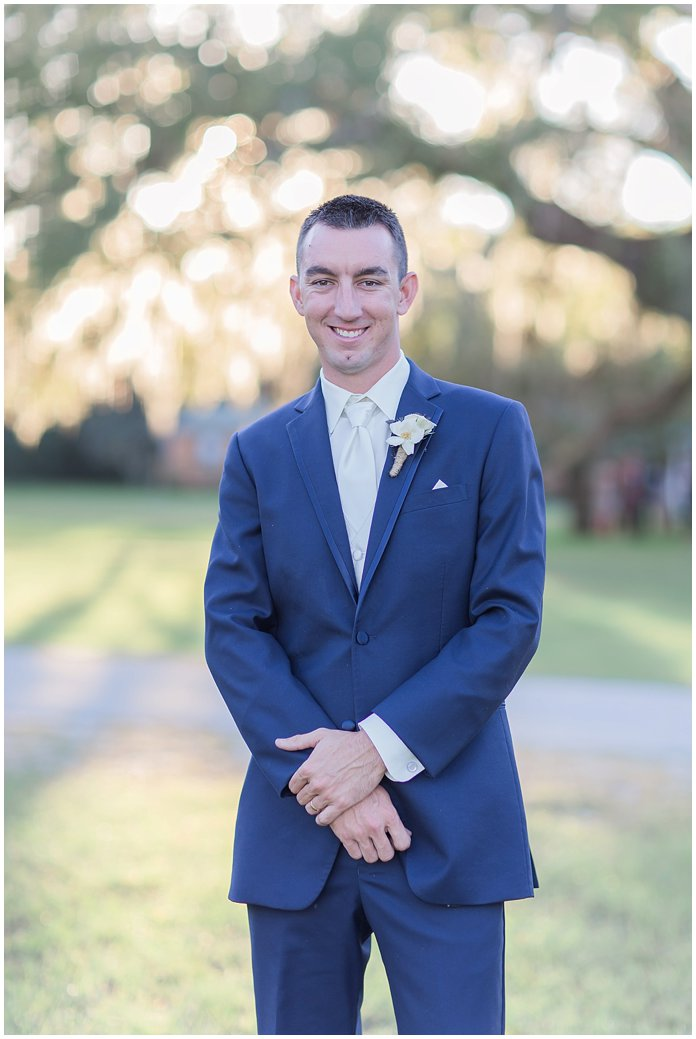 Handsome Groom Portrait in Navy Suit with White Accents and Ranunculus