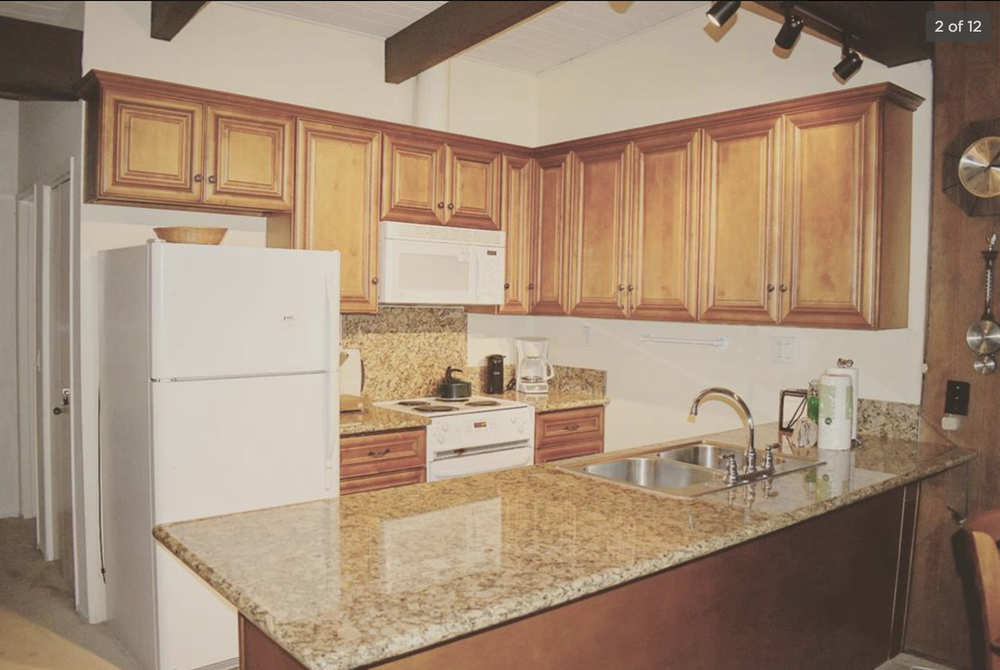 A closer look at the kitchen. White appliances, wood cabinetry with a braided (?) detail, strange cabinet layout, ugly granite. Good space, but desperately in need of an update.