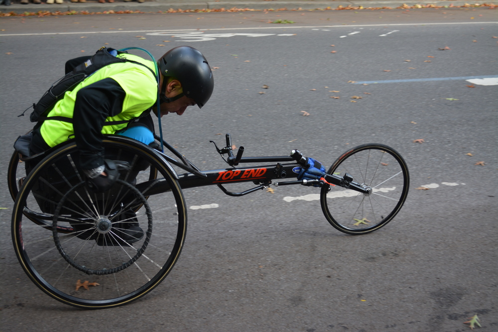 A man with no legs during the NYC marathon going up the hill at the 8 mile mark