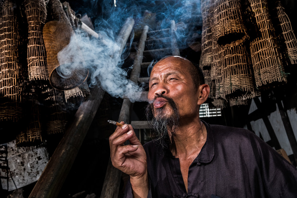China Man Smoking in Home