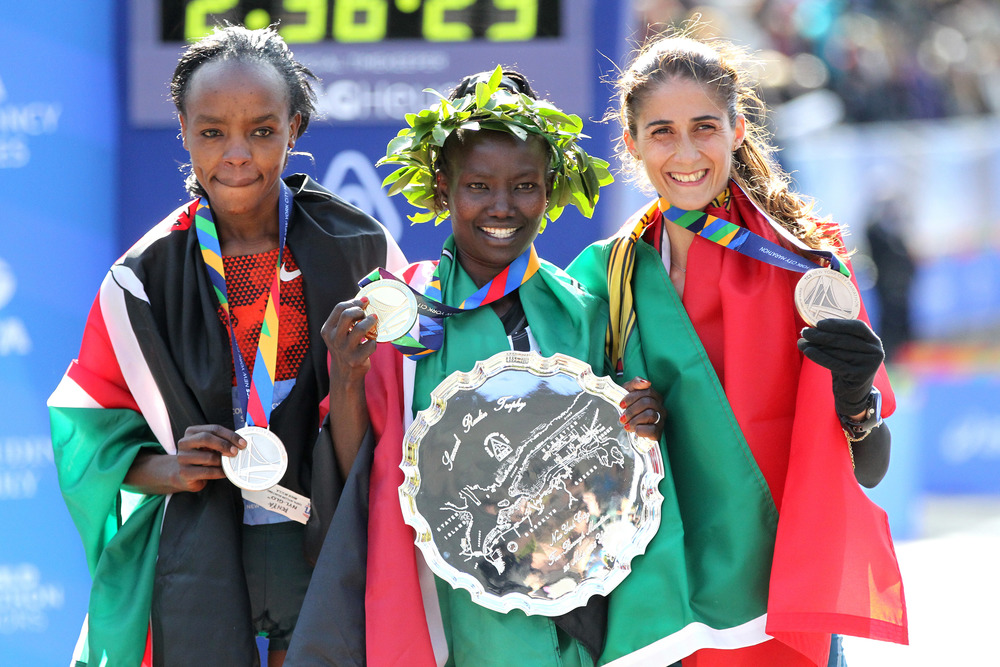 2014 TCS New York City Marathon Champion Mary Keitany (2:25:07) flanked by runner-up Jemima Sumgong and third-place-finisher Sara Moreira. (Credit: PhotoRun/NYRR)