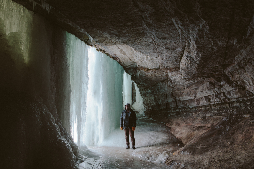 He took me to a waterfall off the Mississippi River that was completely frozen.  We trespassed and hiked behind it, so I could make this rad photo of him.