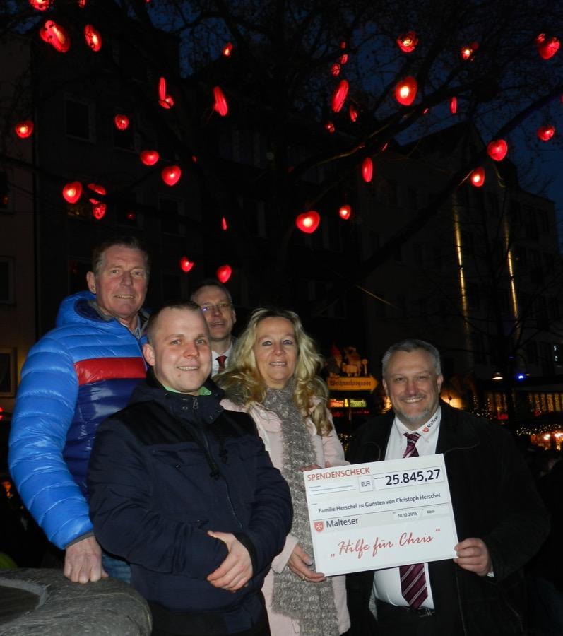 """Im Dezember haben sich die Malteser mit den Eltern von Chris Herschel am Malteser """"Baum der Kinderherzen getroffen"""", um einen Scheck mit dem bisherigen Ergebnis der vielen verschiedenen Spendenaktionen zu überreichen."""