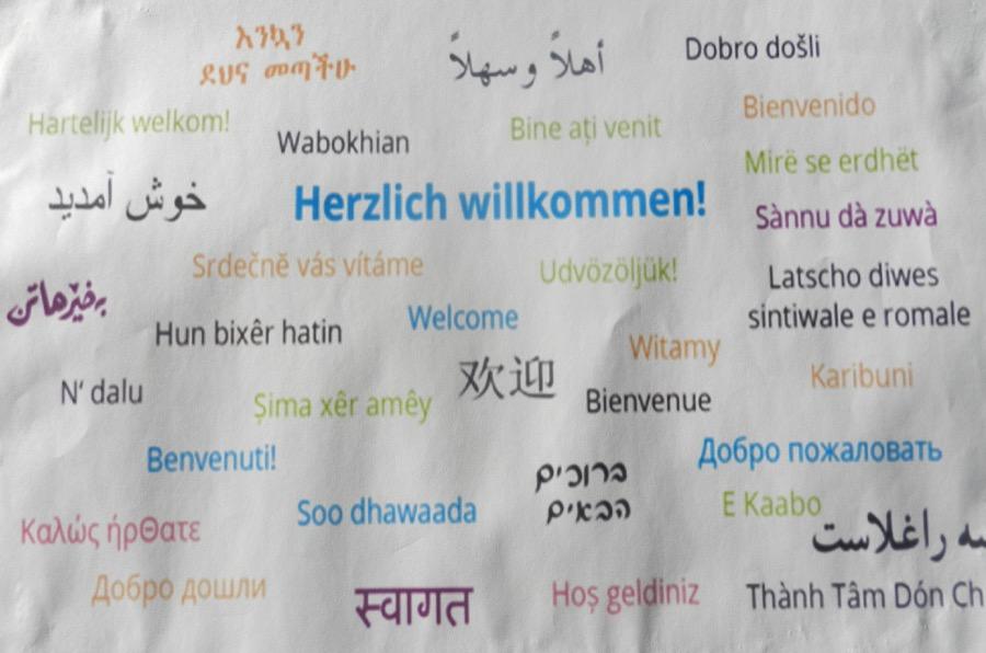 Willkommensplakat in verschiedenen Sprachen aus einer der Flüchtlingsnotunterkünfte, die die Malteser betreuen.