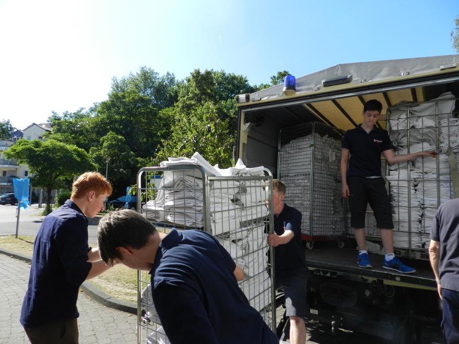 Die Malteser Jugend beim Ausladen der Wäsche an einer Kölner Flüchtlingseinrichtung.