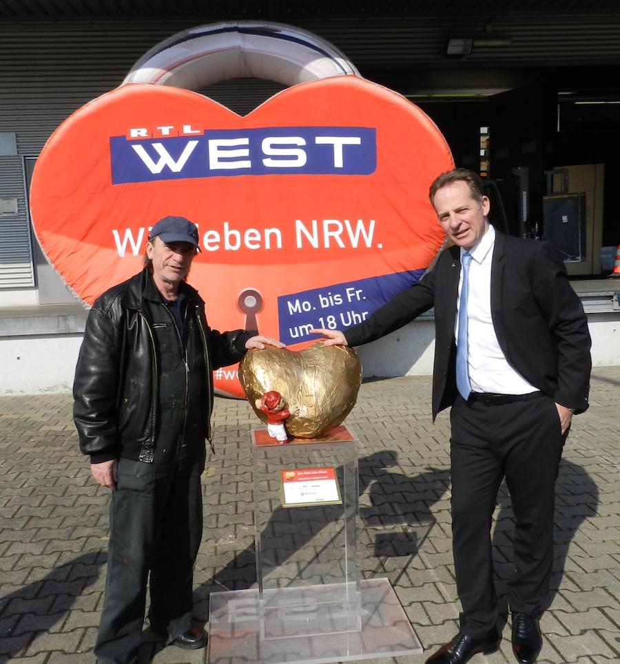 Künstler Anton Fuchs (links) übergibt das große Bronze-Herz an Michael Haiminger, Geschäftsführer der Liebherr-West Haiminger KG.
