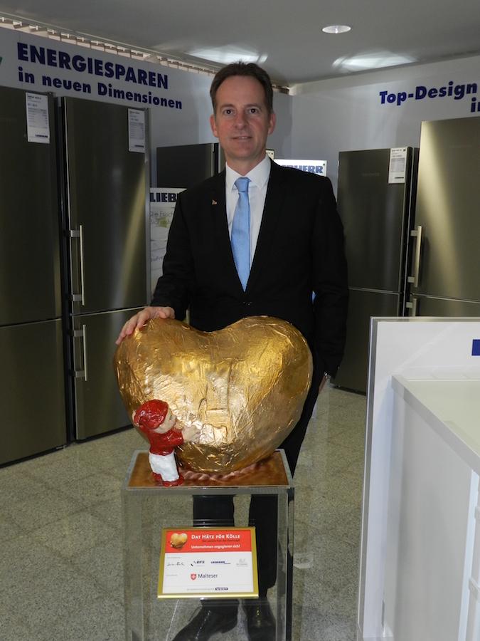 """Geschäftsführer Michael Haiminger mit dem """"Hätz för Kölle"""" im Ausstellungsraum der Liebherr-West Haiminger KG."""
