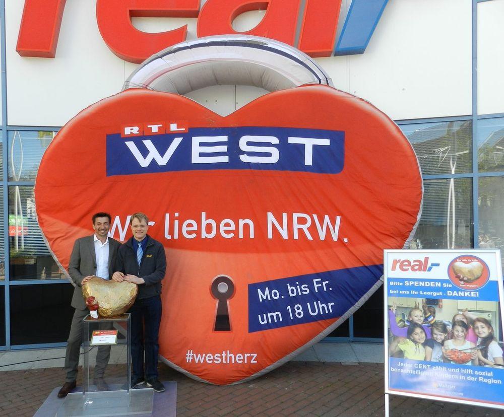 """Thomas Körblein, Geschäftsleiter der real,- SB Warenhaus GmbH, Köln–Sülz (rechts) und Michael Scholl, Geschäftsführer der SKS Versicherungsmakler GmbH & Co KG (links)mit dem """"Hätz för Kölle"""" und dem großen RTL-West Herz."""