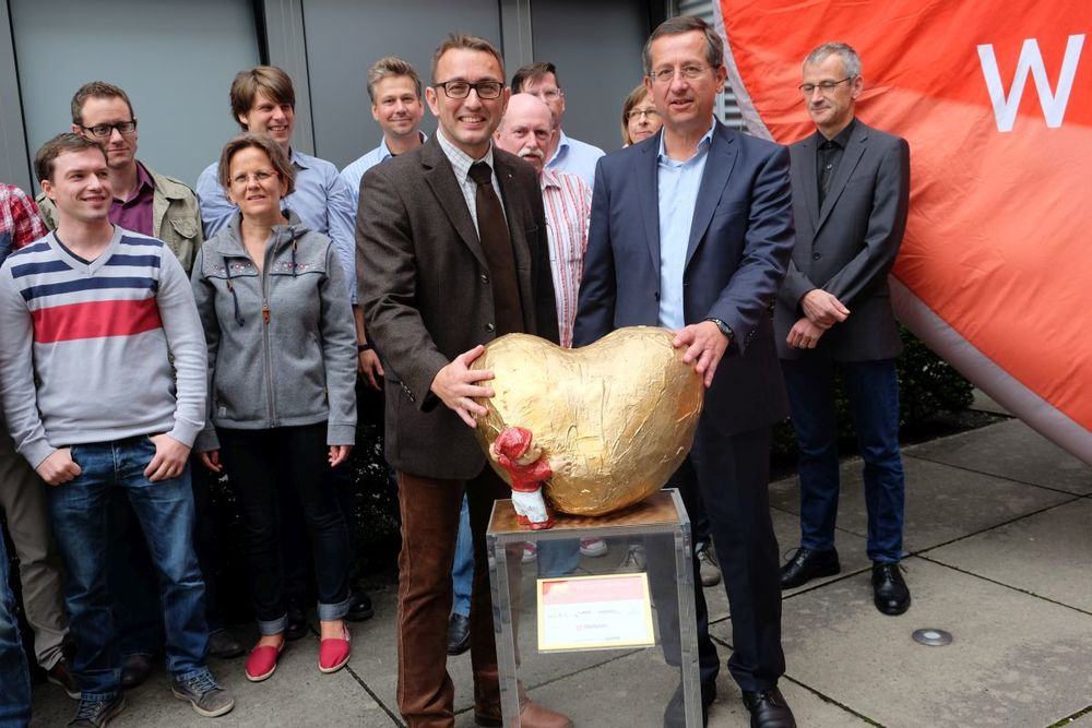 """Jürgen Nisius, Geschäftsführer der Ingenieurbüro Grobecker GmbH (rechts) erhält das """"Hätz för Kölle"""" aus den Händen von Daniel Linzbauer, Geschäftsführer der Primus Service GmbH (links)."""