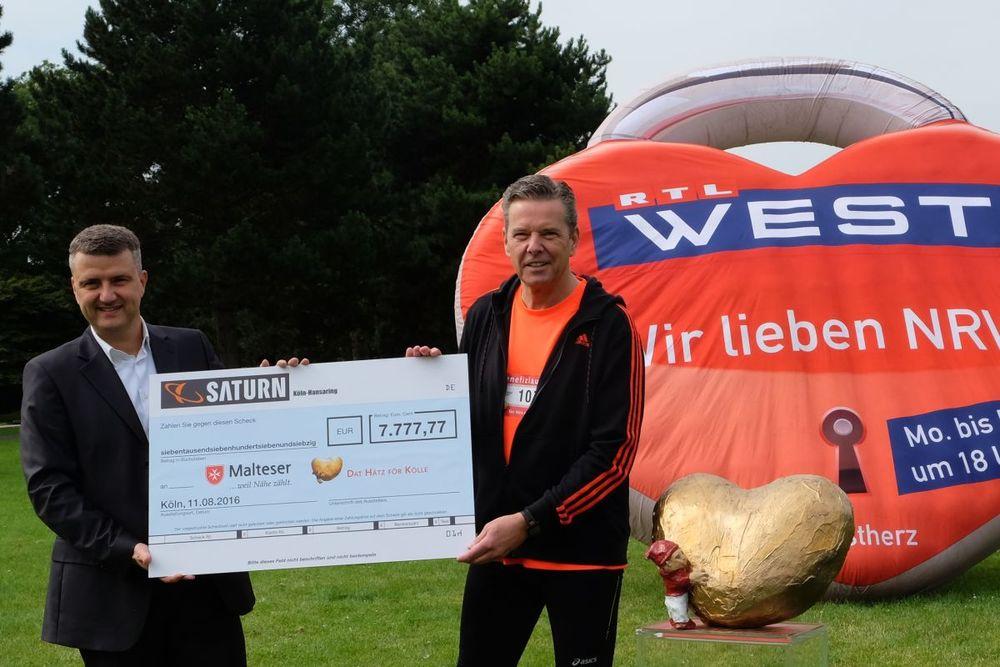 Ralf Schmidbauer, Geschäftsführer der Saturn Techno-Electro-Handelsgesellschaft mbH Köln (links)überreicht den Spendenscheck in Höhe von 7.777,77 Euro an Malteser Diözesangeschäftsführer Martin Rösler.
