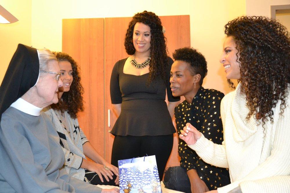 Die vier Musicalstars besuchten auch Patienten auf den Stationen, die nicht in der Lage waren, dem Konzert persönlich beizuwohnen, wie etwas Schwester Assumpta, die seit 60 Jahren als Ordensschwester am Krankenhaus ist und nun selber als Patienten dort behandelt wird. V.l.n.r.: Makeda (Ensemble, Cover Nicky), Chasity Crisp (Ensemble, Cover Rachel), Nyassa Alberta (Alternate Rachel) und Patricia Meeden (Rachel Marron).