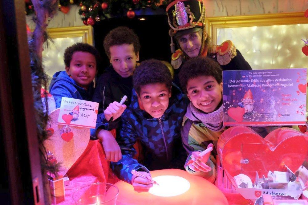 """Die kleinen Musical-Darsteller besuchten die Malteser Weihnachtshütte und malten dort ein neues Herz für den """"Baum der Kinderherzen""""."""