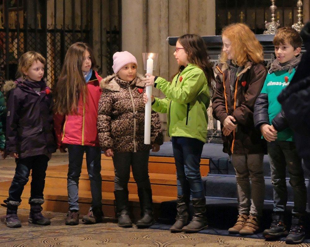 Vor dem Dreikönigenschrein im Kölner Dom, geben die Kinder das Licht weiter.