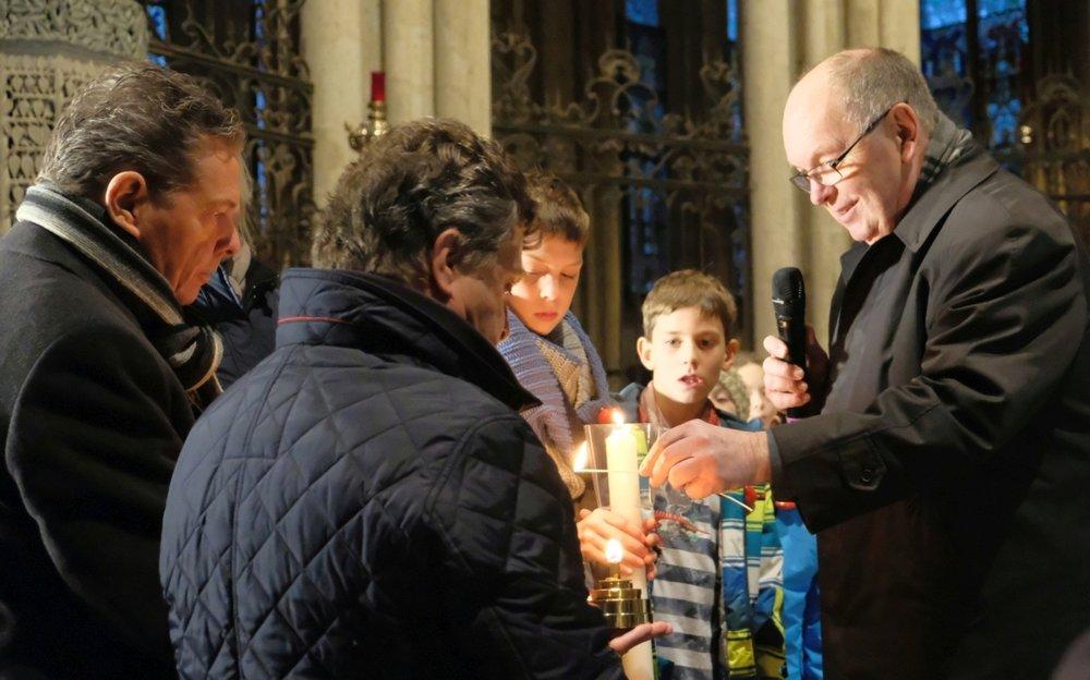 Gemeinsam helfen Martin Rösler (Geschäftsführer der Malteser im Erzbistum Köln), Albrecht Prinz von Croÿ (Diözesanleiter der Malteser im Erzbistum Köln) und Dompropst Gerd Bachner den Kindern beim Entzünden der speziellen Lampen, in denen das Licht weiter getragen wird.