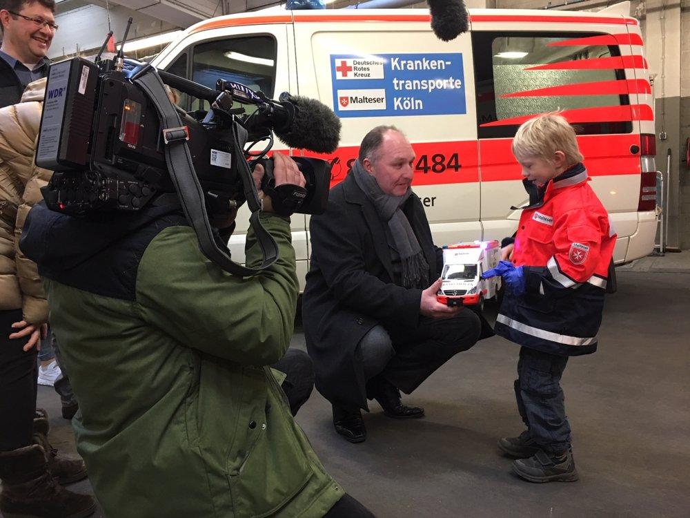 Ralf Schlegelmilch übergibt den kleinen Malteser Herzenswunsch-Krankenwagen an Jonathan.
