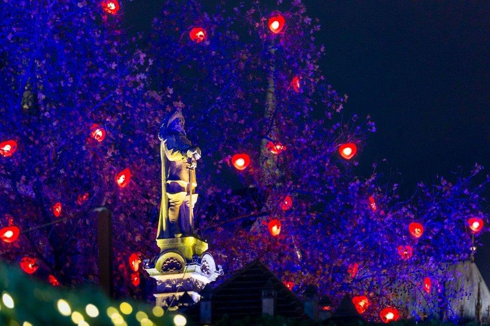 """Der """"Malteser Baum der Kinderherzen"""" leuchtet über dem Weihnachtsmarkt Kölner Altstadt neben der Malteser Weihnachtshütte."""