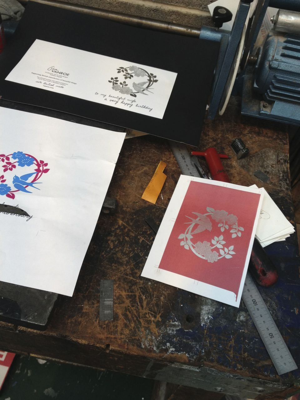 The Rose & Swallow card on the print workshop table, laying out print and testing foil.
