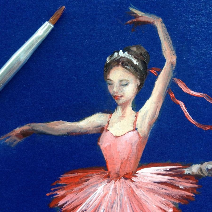 The tiniest ballerina, on my studio desk. She's painted in traditional oil paint, and I use brushes made for tiny nail art designs. Here you can see the nail art brush for scale!