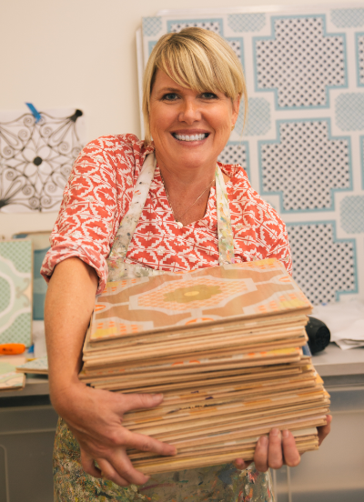 Sally Bennett Owner and creator of Mirth Studio holding hand painted hardwood tiles