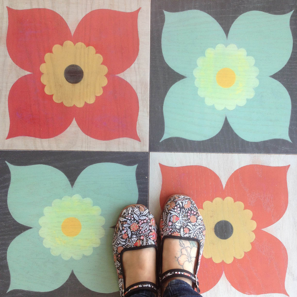 Poppy pattern in coral and mint repeated as hardwood floor tile in 12x12