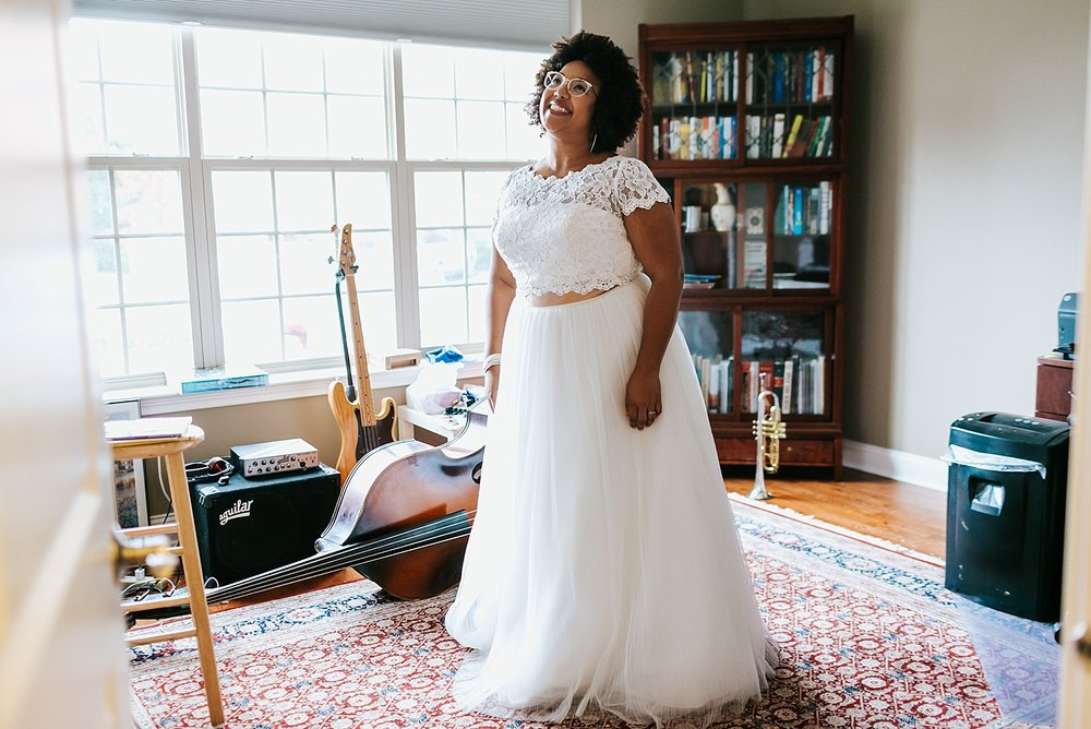 Bride smiling in a window lit room at Naval Square, Philadelphia by Danfredo Photos + Films