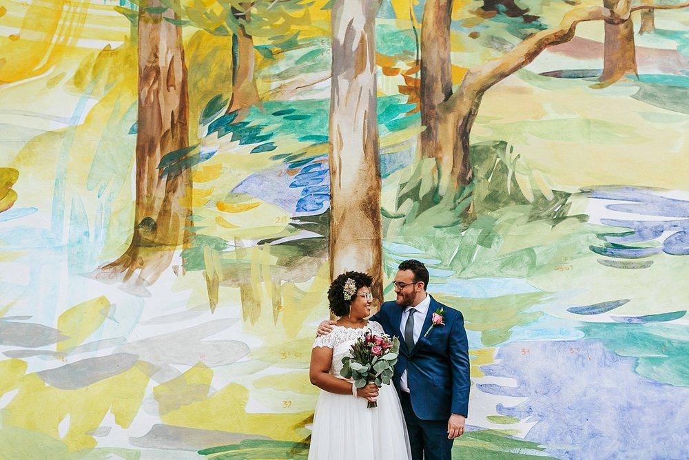 Bride and groom standing in front of a mural at the Fleisher Art Memorial by Danfredo Photos + Films
