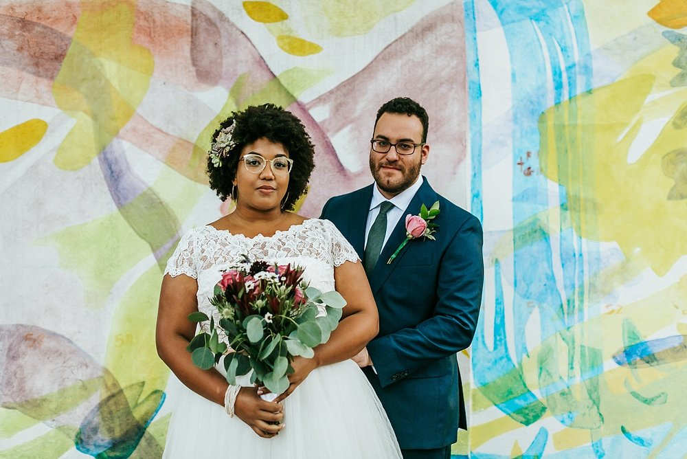 Interracial bride and groom standing in front of a mural at Fleisher Art Memorial by Danfredo Photos + Films