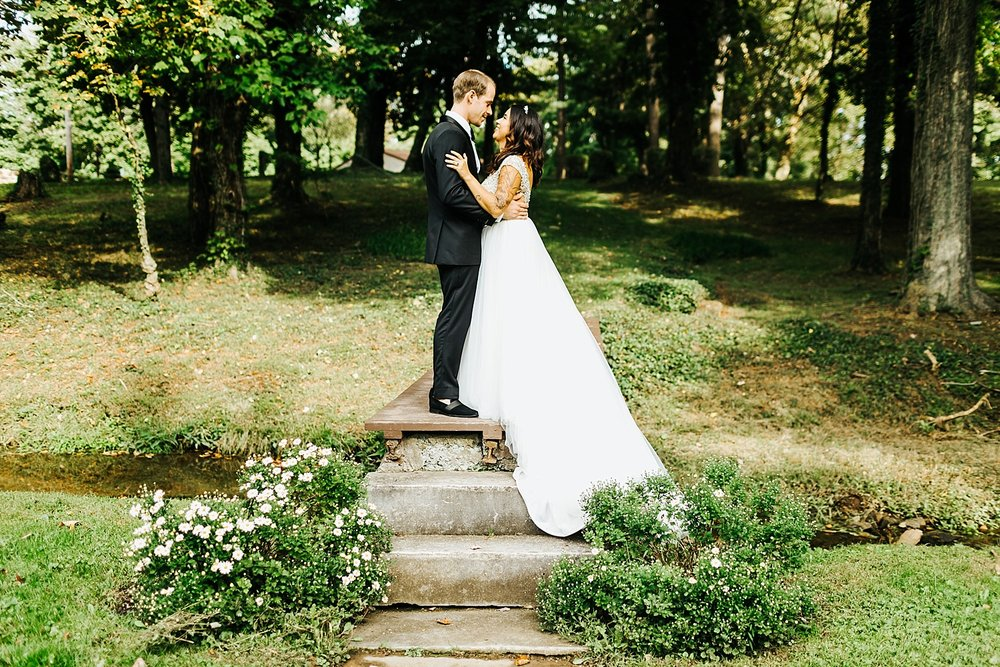 Bride and groom looking into each others eyes, holding each other in a park surrounded by trees